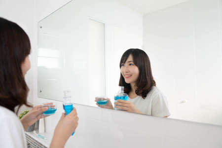 Attractive asian woman smiling and holding mouthwash in front of mirror bathroom. Oral hygiene routine for freshness breath, prevent plaque and gum disease. Dental health care concept.
