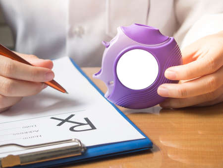 Doctor hands holding medicine dry powder inhaler and writing medical prescription on rx form for treatment asthma/COPD diseases on physician's desk at hospital. Health care and medication concept. Foto de archivo