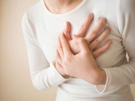 Heart attack/problems. Young female suffering from severe chest pain. Warning signs of unstable angina or myocardrial infarction disease. Health care and cardiological concept. Close up. Copy space. Stock Photo