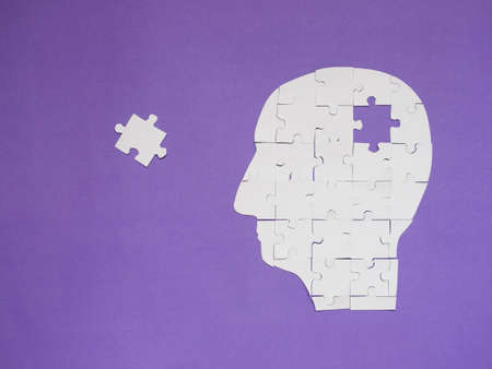 Head brain white puzzle with missing pieces from jigsaw puzzle on purple background. Creative idea for memory loss, dementia, Alzheimer's disease and mental health concept. Copy space.