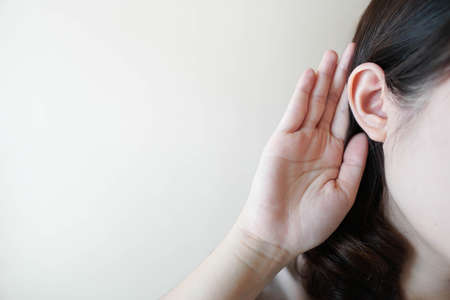 Close up of woman holding her hand near ear over white background w/ copy space for your text. Concept of gossip, interesting news or hearing loss.