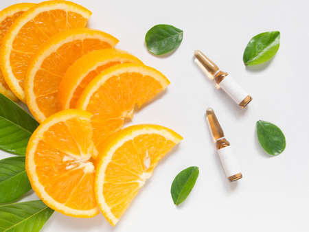 Top view of vitamin C brown ampule for injection with fresh juicy orange fruit slides and green leaves on white table. Vitamin synthetic or natural nutrition choices concept. Beauty product mock-up.