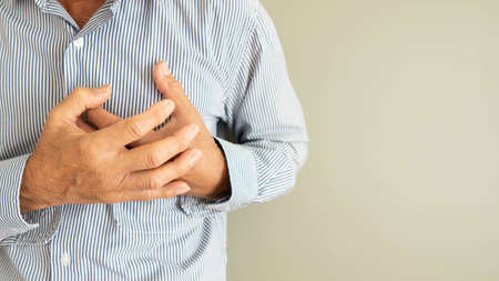 Heart attack problems. Senior man suffering from severe chest pain. Warning signs of unstable angina or myocardrial infarction disease. Health care and cardiological concept. Close up. Copy space.