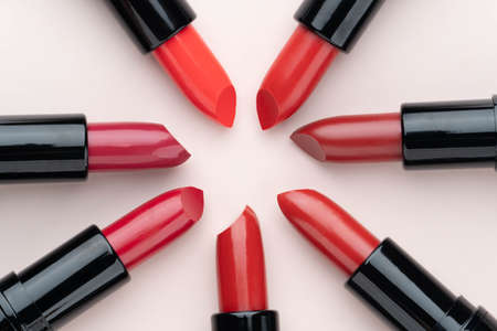 Red lipsticks of different shades arranged in a circle on beige background. Makeup and cosmetics concept. Close up. Flat layout.