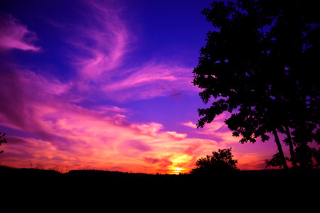 Red and purple sunset with rays of sun that stretch in the sky Stock Photo