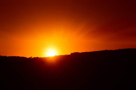 Sunset with sun seen a little behind a hill and that expands the last rays in the beautiful sky turned orange Stock Photo