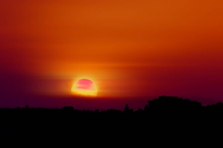 Beautiful red sunset with the sun and filtered by haze Stock Photo