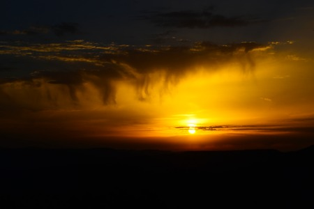 Beautiful yellow sunset with clouds falling threadlike