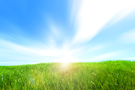 Beautiful hill with green grass clouds in the blue sky and the sun low on the horizon Stock Photo