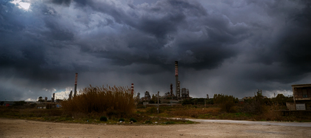 Gray Clouds of Storm over two smokestacks of an oil industry
