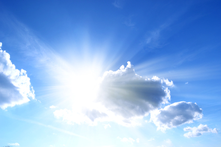 Sun high in the sky with sprouting rays in front of clouds