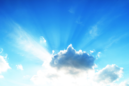 Sol alto en el cielo con rayos brotando frente a las nubes