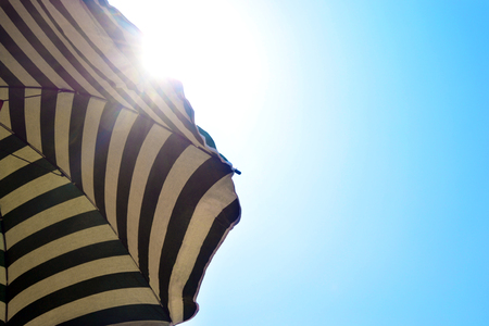 beach umbrella with sunbeams in backlight with the blue sky _ summer and sea