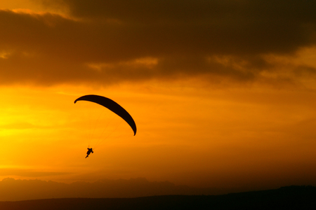 Paragliding silhouette at sunset yellow orange