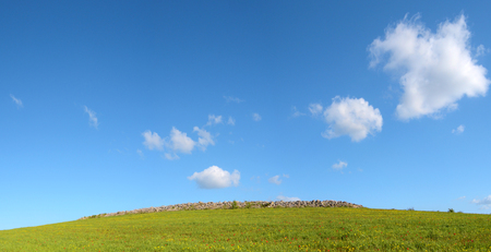 Green hill with clouds in the blue sky Imagens