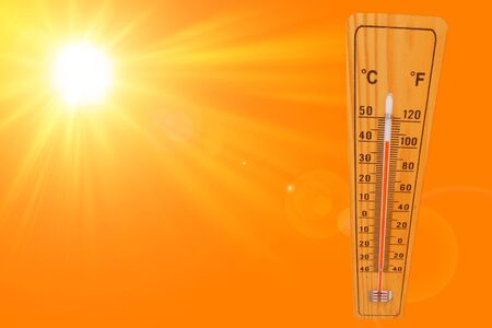 Sunny summer background with the thermometer marking a temperature over 40 degrees and bright sun on an orange background