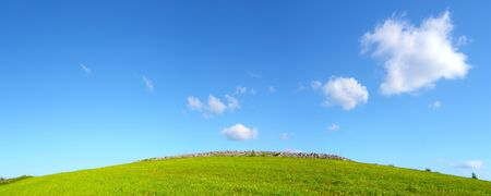 Hill with green grass and a blue sky with heaps