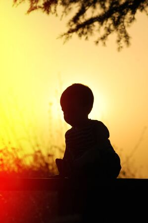 Silhouette of a child at sunset sitting on a bench