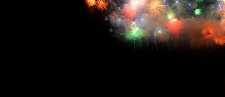 Colorful fireworks that explode and fill the darkness of the night sky on a black background with the words 2020 happy new year. Imagens