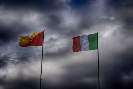 Italy flag and Sicily flag with dramatic clouds as the background