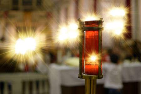 Votive candle lit inside a church representing divine light.