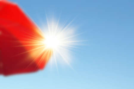 Parasol with sun rays.Red beach umbrella sheltering the strong summer sun in the blue sky.