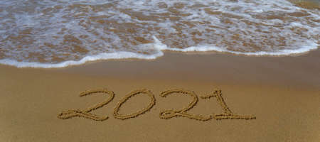 Happy new year 2021 written in the sand. Happy new year 2021 written in the sand by the sea.