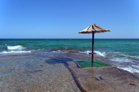 Umbrella in the sand on the deserted beach.Beach umbrella.
