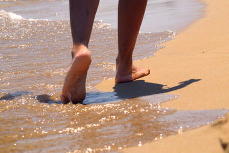 Woman walking barefoot on the sand leaving footprints on the golden beach.Female legs walk by the sea.Vacation, summer vacation or vacation concept.Bare feet of a woman walking along a sandy beach with the waves.travel and freedom. Stok Fotoğraf - 166707689