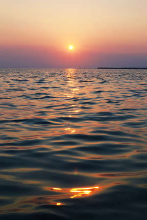 Sunny sunset over the sea stretching to the horizon