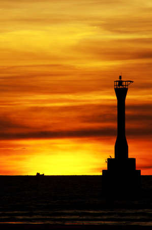 Sunset over the lighthouse on the tropical island of thailand. photo