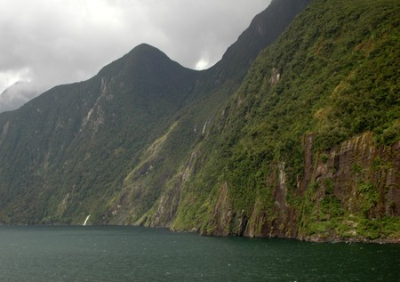 steep mountain walls, cliffs over the water on rainy day Imagens