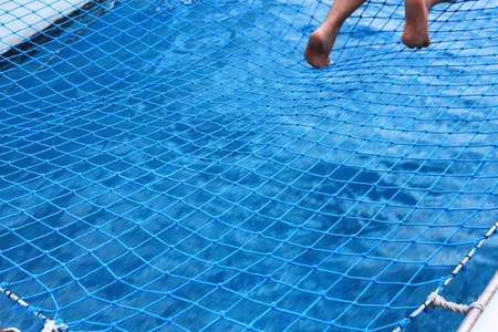 Human feet over the net and water on catamaran