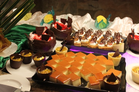 Sweet buffet display; sliced cake with yellow glazee Imagens