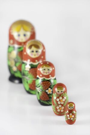 Matryoshka dolls ordered from large to small, with the focus on the small doll in front
