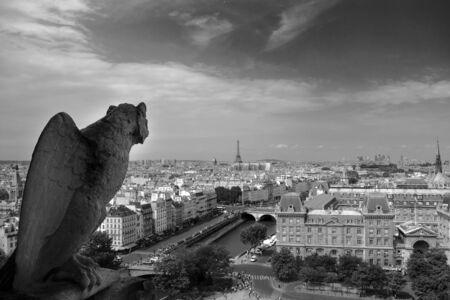 Gargola dans la cathédrale Notre Dame de Paris, avec la tour Eifel en arrière-plan, photo en noir et blanc.