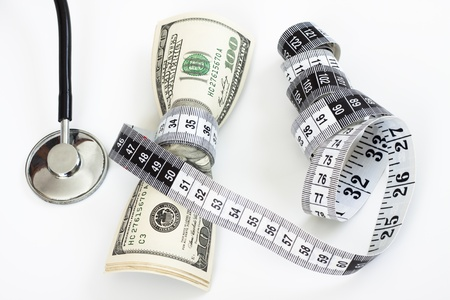 a bunch of dollar bills tighten by a measuring tape  and a stethoscope on white background Stock Photo - 9303360