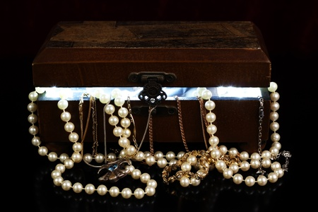 tresure: tresure chest with open lid light from within and jewelry with reflection