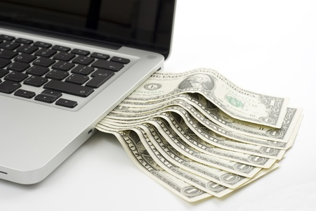 dolar: un billetes dolar saliendo de una ranura de parte de leptop Foto de archivo