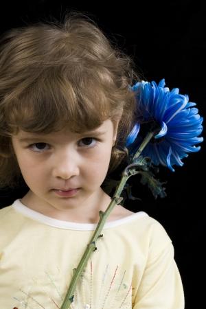 blonde litle girl holding blue flower facing forword photo