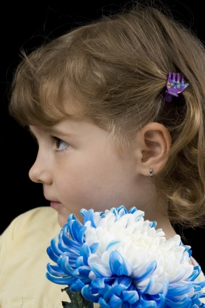 portret: little girl portret holding a blue flower facing sideway Stock Photo