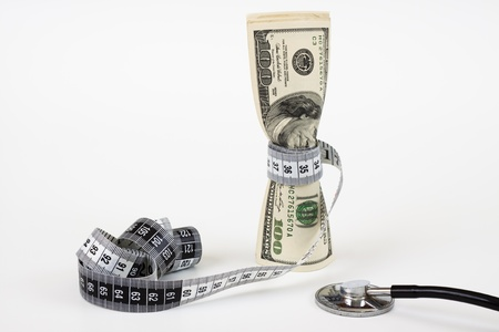 a bunch of dollar bills tighten by a measuring tape  and a stethoscope on white background Stock Photo - 9313482