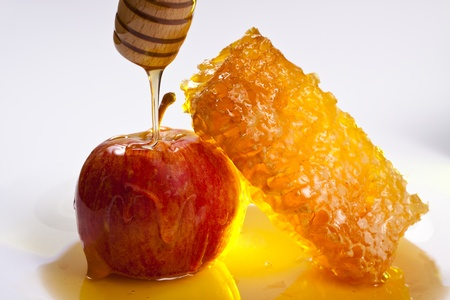 jewish new year: red apple with honeycomb and pooring honey on it white background