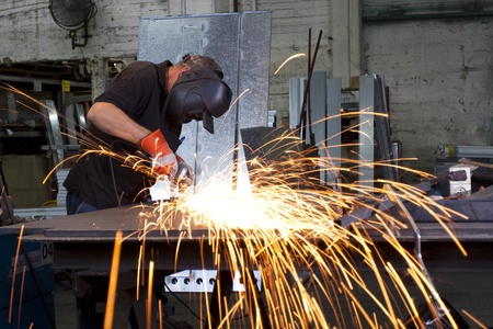 sparks frying over the working table during metal grinding photo