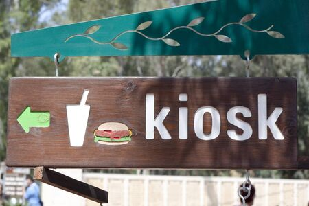 a wood sign with a green arrow with a hamburger and kiosk photo