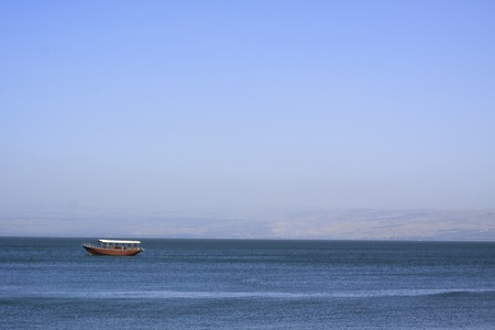 boat am the sea of galilee in a summer day with blue sky and water with the golan hight  in the background photo