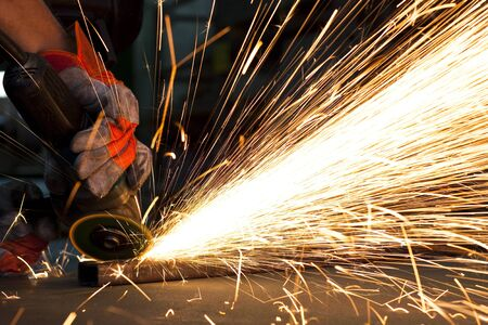 sparks while grinding in a steel factory photo