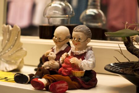 next to each other: grandmother figure doll and a grandfather doll sitting next each other