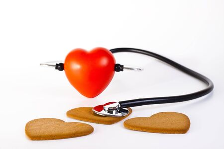 red hart wits a stethoscope  examining brown ginger bread hearts photo