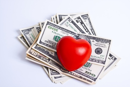 red heart and dollar bills on white background photo